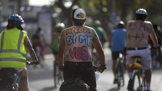"""A cyclist, with a message written on his back that reads in Spanish, """"Now you see me,"""" takes part in a """"naked"""" bike ride event in Caracas, Venezuela, Saturday, June 13, 2015. The clothing-optional campaign, """"Let's see if you see me"""" draws attention to cyclist safety. (AP Photo/Ariana Cubillos)"""