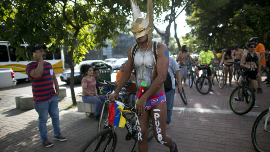 """A masked cyclist takes part in a """"naked bike ride event"""" in Caracas, Venezuela, Saturday, June 13, 2015. The clothing-optional campaign, """"Let's see if you see me"""" draws attention to cyclist safety. (AP Photo/Ariana Cubillos)"""