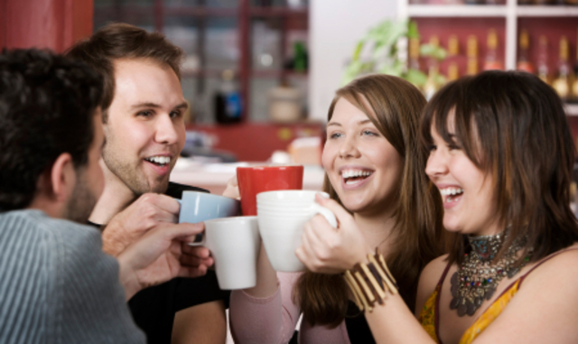 Young toasting friends with coffee cups in a cafe